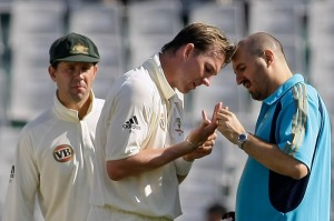 Australian bowler Brett Lee, centre, is attended to by team physiotherapist, 2010.